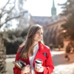 woman-in-red-coat-holding-notebooks-and-coffee-cup-3755760
